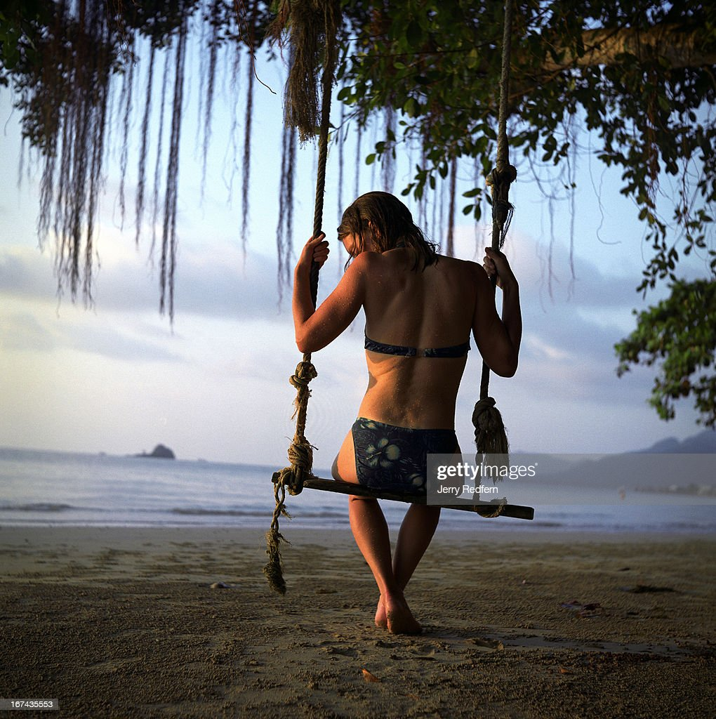 A tourist sits in a wooden swing hanging from a tree..
