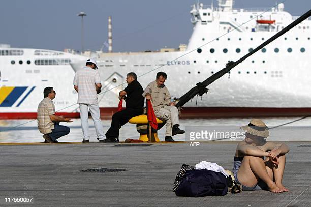 A tourist sits in the port of Piraeus on June 28 2011 as around 200 militants of communistaffiliated unions prevent ferries from leaving the harbor...