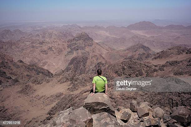 A tourist sits on the edge o Mount Katherine one of a group of tourists hiking through the mountains of South Sinai on April 18 2015 near St...