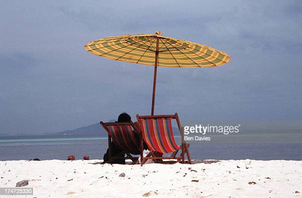 A tourist sits under an umbrella in Maya Bay on Ko Phi Ph in the South of Thailandi Brilliant turquoise sea and white sparkling sandy beaches have...