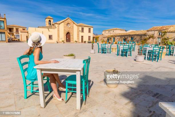 tourist sitting at a bar table in the main square of marzamemi,a small fishing village, siracusa province, sicily, italy, europe - square stock pictures, royalty-free photos & images