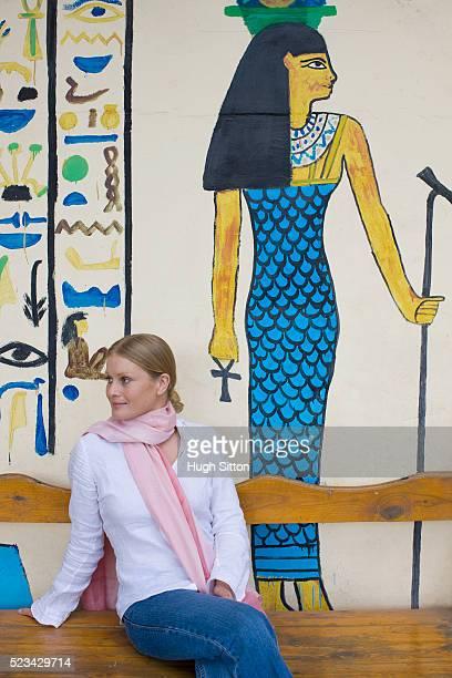tourist sitting by egyptian style mural - hugh sitton imagens e fotografias de stock