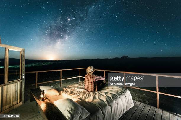 Tourist sitting in bed outdoors under a starry sky
