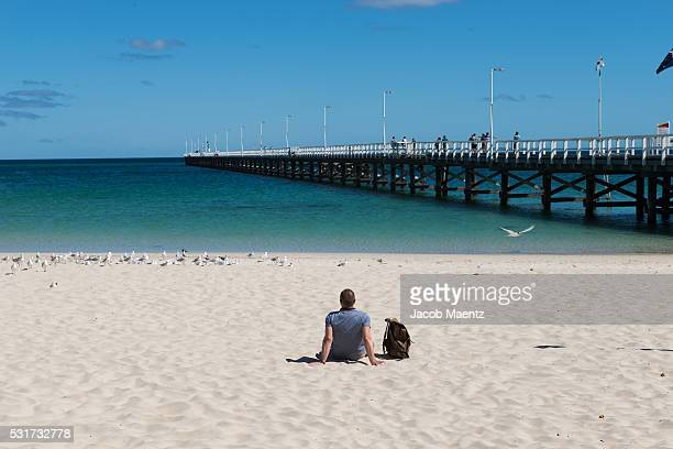 A tourist sitting in front of the Busselton Jetty
