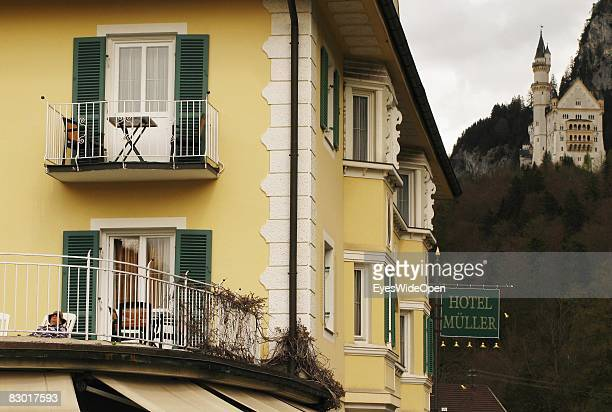 A tourist sitting on a balcony of a Hotel near castle Neuschwanstein on September 24 2008 in Hohenschwangau Ostallgaeu Germany The castle was rebuilt...