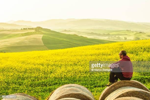 Tourist sitting on a bale hale, Tuscany, Italy.