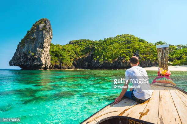 tourist sitting on a longtail boat in phi phi island, thailand - phi phi islands stock-fotos und bilder