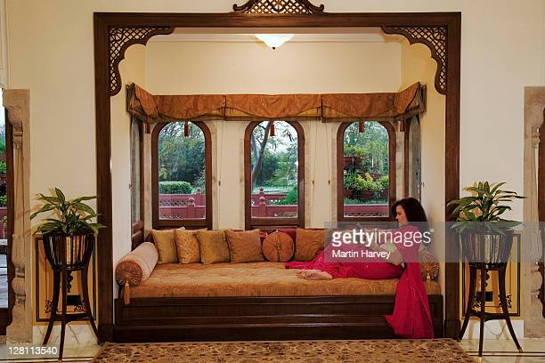 tourist sitting on couch by bay window of a historical suit in taj rambagh palace hotel in jaipur, part of the taj hotel group. india. (mr) - palast stock-fotos und bilder