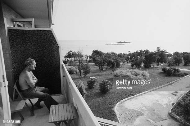Tourist sitting on the belcony of his hotel in Porec in Croatian