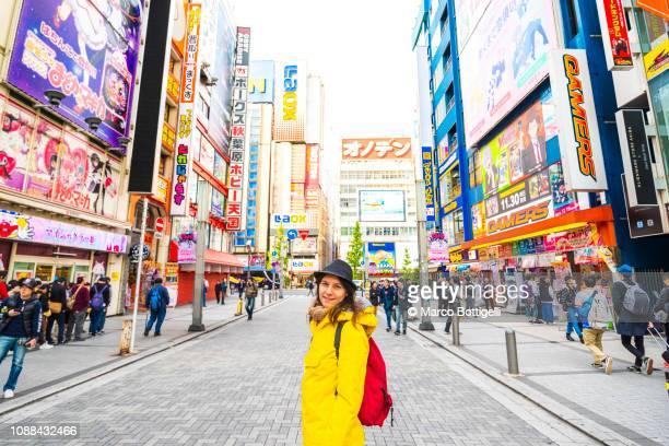 tourist smiling at camera in akihabara electronic town, tokyo, japan - akihabara stock pictures, royalty-free photos & images