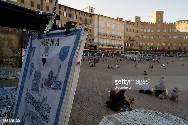 A tourist souvenir stall displays goods as visitors sit and relax on the Piazza del Campo in Siena Italy on Friday Aug 5 2016 Banca Monte dei Paschi...