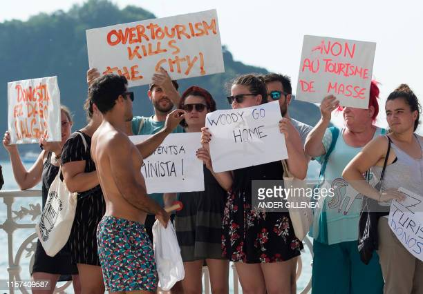 A tourist speaks with protesters that demonstrate against the shooting of Woody Allen's new film in the Spanish Basque city of San Sebastian on July...