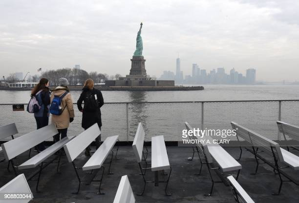 Tourist stand aboard the Miss Ellis Island Ferry Boat as the first visitors arrive Monday morning after the reopening of the Statue of Liberty...