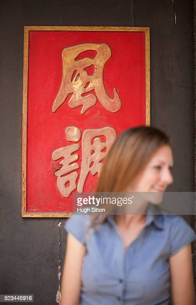tourist standing in front of a chinese sign outside a buddhist temple, singapore - hugh sitton stock-fotos und bilder