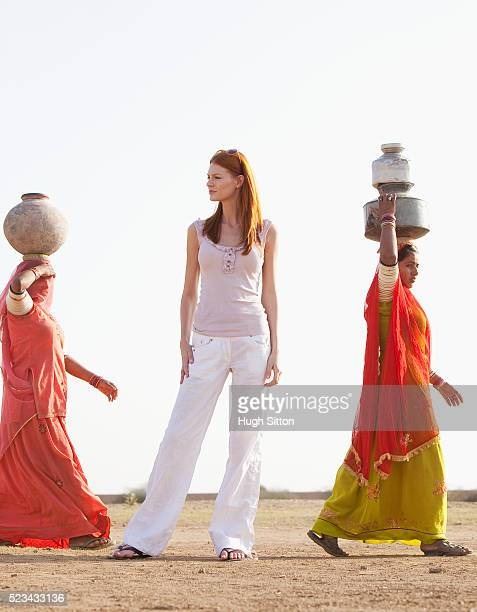 tourist standing in the desert while local women water jugs - hugh sitton india stock pictures, royalty-free photos & images