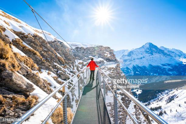 tourist standing on a suspended walkway in the swiss alps, grindelwald, switzerland - parapetto barriera foto e immagini stock