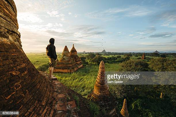 tourist standing on bagan pagoda during sunrise in myanmar - tempel stock-fotos und bilder