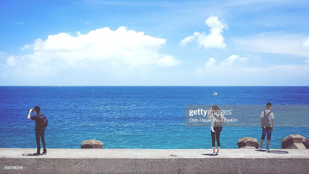 Tourist Standing On Retaining Wall Of Sea Against Cloudy Sky : Foto stock