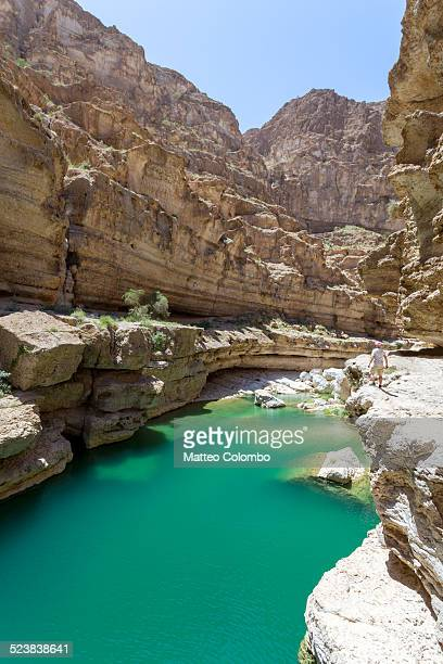 Tourist standing on the edge of cliff in Wadi shab
