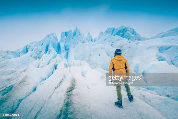 tourist standing on the perito moreno glacier, argentina - personas cabeza grande fotografías e imágenes de stock