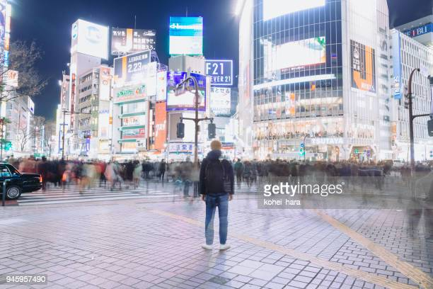 a tourist standing on the shibuya crossing at night - shibuya ward stock pictures, royalty-free photos & images