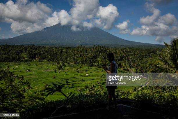 KARANGASEM BALI INDONESIA SEPTEMBER 29 A tourist stands and looks on at mount Agung on September 29 2017 in Karangasem regency Island of Bali...