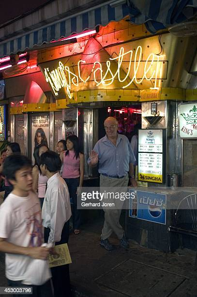 A tourist stands by the entrance to a gogo bar in the infamous red light district of Patpong in central Bangkok The Thai capital has become renowned...