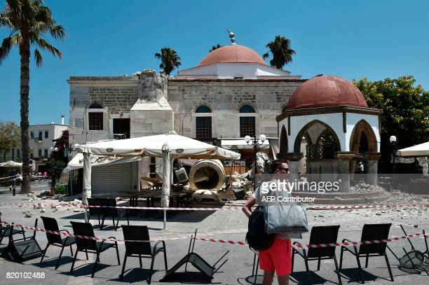 A tourist stands in front of a partially damaged mosque in the central square of the island of Kos on July 21 following a 65 magnitude earthquake...