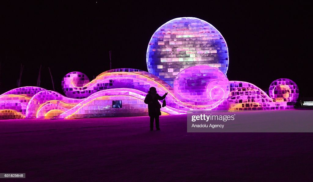 A tourist stands in front of an illuminated ice sculpture during the 33rd Harbin International Ice and Snow Festival at Harbin Ice And Snow World in Harbin, China on January 16, 2017. The Festival, established in 1985, is held annually on January 5 and lasts over a month.