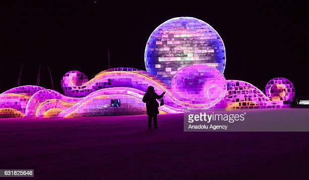 A tourist stands in front of an illuminated ice sculpture during the 33rd Harbin International Ice and Snow Festival at Harbin Ice And Snow World in...