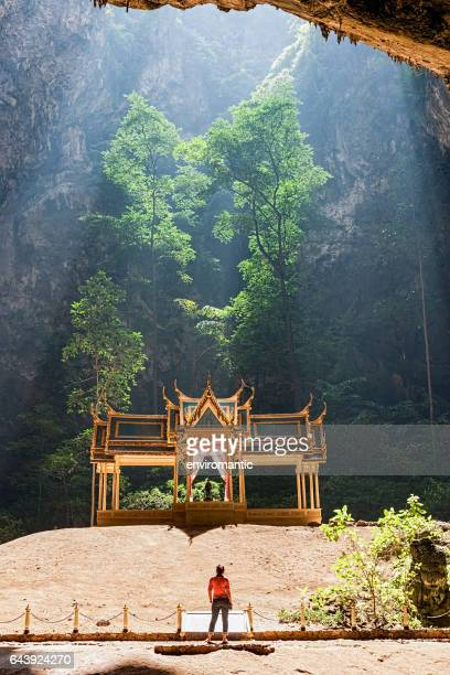 Tourist stands in front of the Royal Sala in Phra Nakorn Cave in Khao Sam Roi Yot, Prachuab Khiri Khan, Thailand.