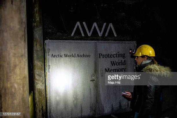 Tourist stands next to the Arctic World Archive that will include the GitHub Arctic Code Vault in former coal mine number 3 on Svalbard archipelago...