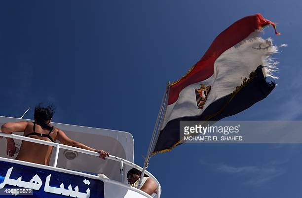 A tourist stands on a boat near the Egyptian national flag in the Red Sea resort of Sharm elSheikh on November 8 2015 Moscow and London ramped up...