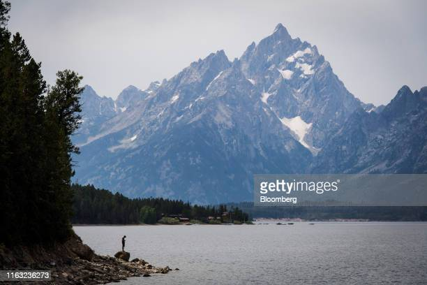 Tourist stands on a rock along the shore of Jackson Lake in Jackson Hole, Wyoming, U.S., on Thursday, Aug. 22, 2019. Over the past two decades,...