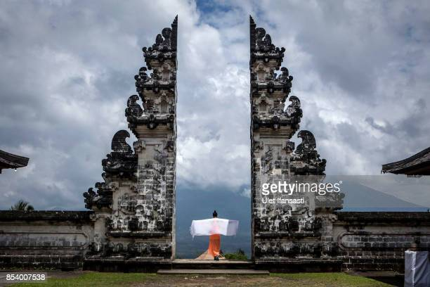 KARANGASEM BALI INDONESIA SEPTEMBER 26 A tourist stretches out a shawl as they stand at the gate of Penataran Agung Lempuyang temple with mount Agung...