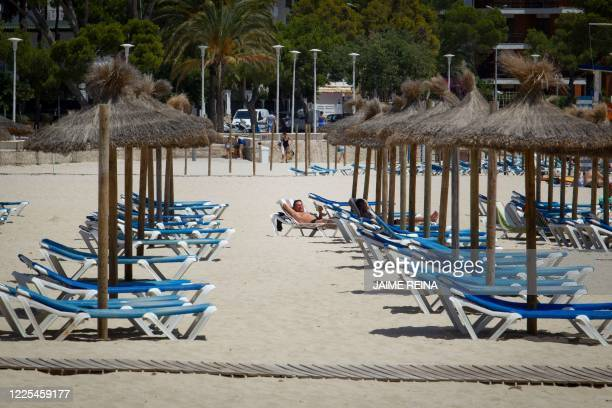 A tourist sunbathes at Es Carregador Beach in Calvia on the Spanish island of Mallorca on July 8 2020 The Balearic Islands are expecting a wave of...