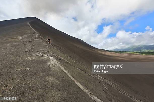 Tourist surfing down ash slope of Mt Yasur vocano
