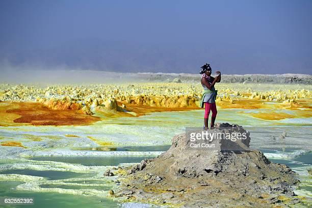 Tourist take a photograph of a sulphur lake in the Danakil Depression on January 23, 2017 near Dallol, Ethiopia. The depression lies 100 metres below...