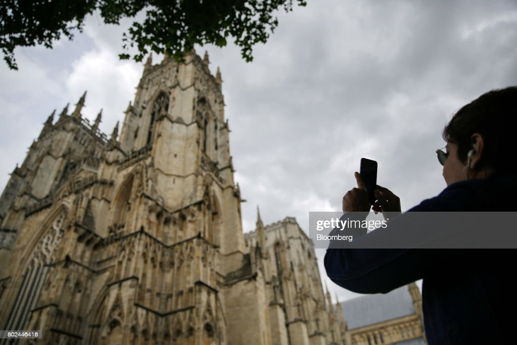 A tourist take a photograph of York Minster cathedral in York, U.K., on Monday, June 26, 2017. Economic growth slowed to 0.2 percent in the first quarter of the year and only strong international trade will prevent a recession going forward, CEBR Deputy ChairmanDouglas McWilliamssaid. Photographer: Matthew Lloyd/Bloomberg via Getty Images