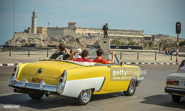 Tourist take a ride in a fully restored Mercury along the coast in Havana on March 18 2013 Luxury is slowly reappearing in Cuban society after half a...