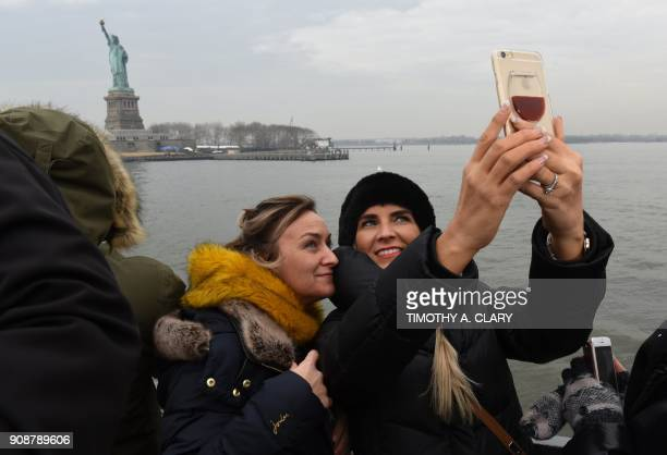 Tourist take pictures aboard the Miss Ellis Island Ferry Boat as the first visitors arrive Monday morning after the reopening of the Statue of...