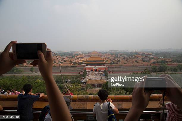 Tourist take pictures from Jingshan Park at the Forbidden City in Beijing China July 24 2015