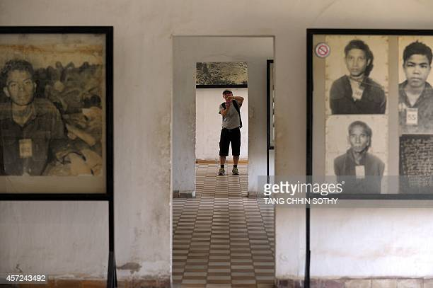 A tourist takes a photo beside portrait photos of the victims of Khmer Rouge displayed for visitors at the Tuol Sleng genocide museum in Phnom Penh...