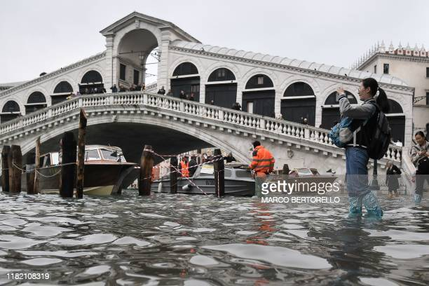 A tourist takes a photo from the flooded embankment by the Rialto bridge after an exceptional overnight Alta Acqua high tide water level on November...