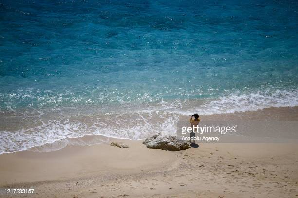 Tourist takes a photo in Kaputas beach as beaches reopened to public in accordance with the social distance rules after the government decided to...