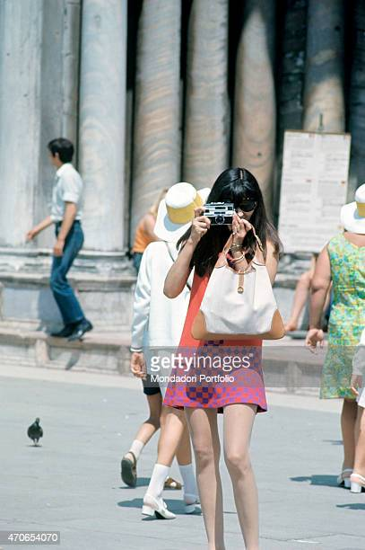 A tourist takes a photo of something in an Italian city the report is on the lonely women around the Italian cities Italy August 1968
