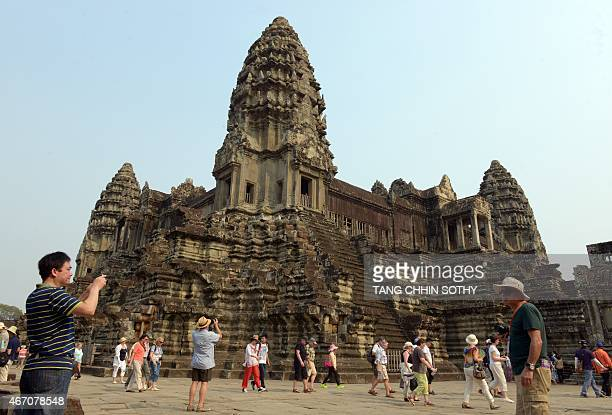 A tourist takes a photo of the Angkor Wat temple in Siem Reap province on March 20 2015 US First Lady Michelle Obama flew into Cambodia at the...