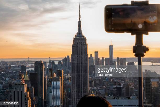 Tourist takes a photo of the Empire State Building and the New York City skyline from Top of the Rock, the observation deck on top of Rockefeller...