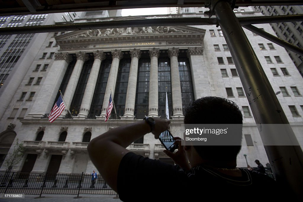A tourist takes a photograph in front of the New York Stock Exchange (NYSE) in New York, U.S., on Friday, June 28, 2013. U.S. stocks fell, after the biggest three-day rally since January for the Standard & Poor's 500 Index, before data on consumer sentiment and business activity as investors weighed statements from Federal Reserve officials. Photographer: Scott Eells/Bloomberg via Getty Images