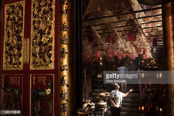 A tourist takes a photograph inside the Man Mo Temple in the Sheung Wan neighborhood on July 16 2019 in Hong Kong China Sheung Wan and the...